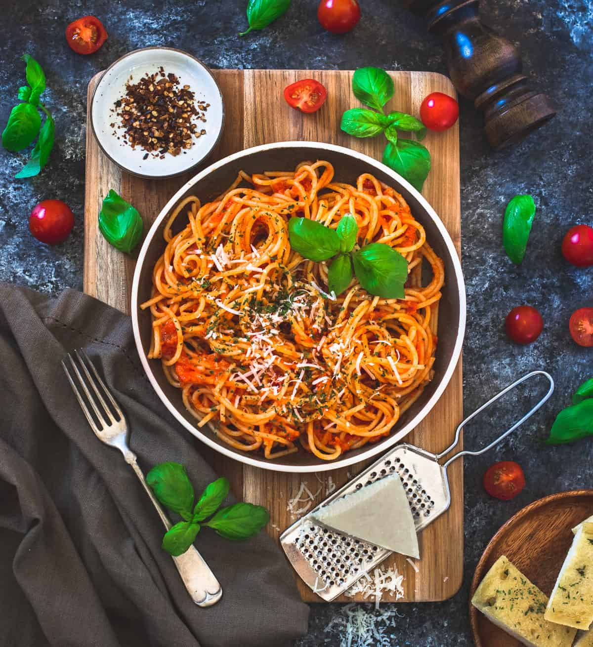 Pasta arrabiata served with cheese , red chili flakes and a fork