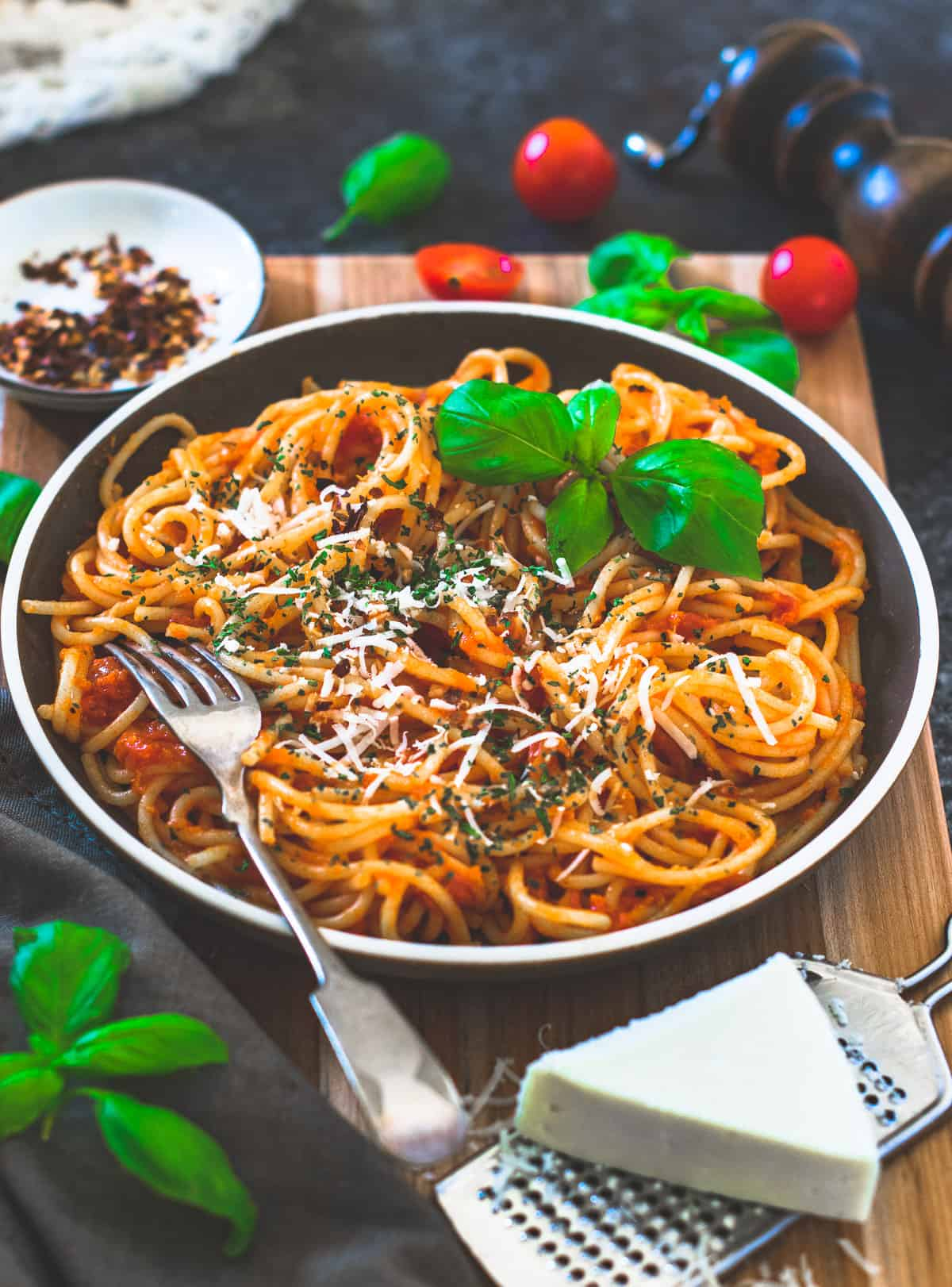 Spaghetti on a brown plate with cheese