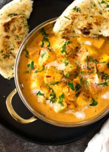 Shahi paneer on a black plate served with warm naan.