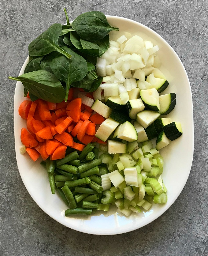 Ingredients of minestrone soup namely spinach, carrots, zucchini, beans and onion.
