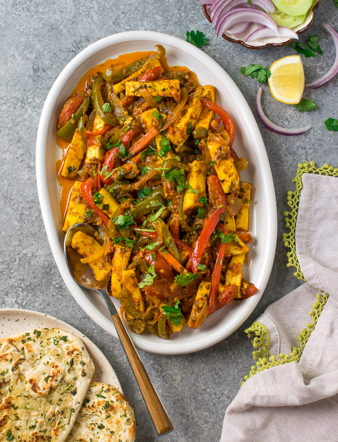 Vegetable Jalfrezi on a serving dish with naan on the side.