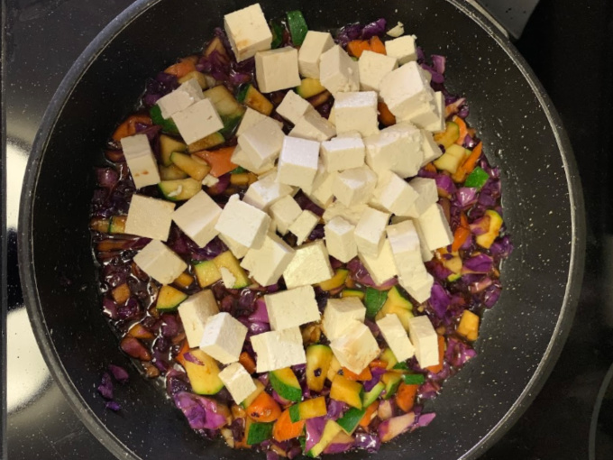 Adding tofu to the pan.