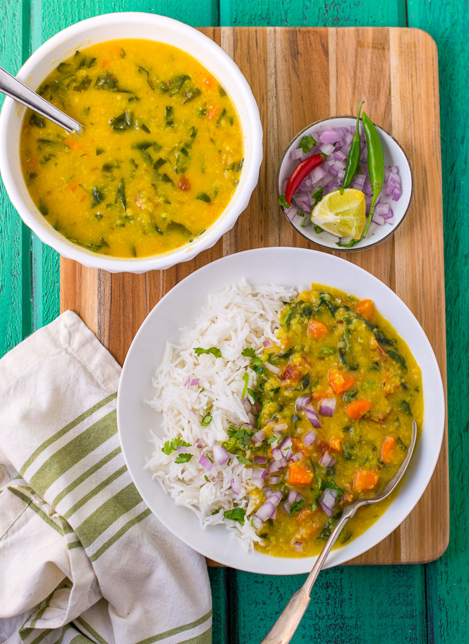 Dal and rice in a white bowl with carrots and onions