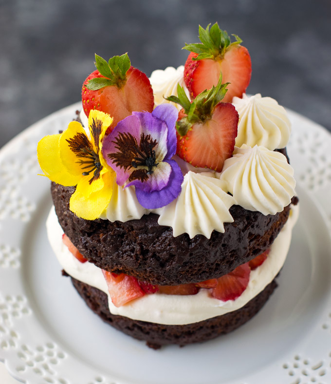 Cake decorated with fresh fruits and flowers