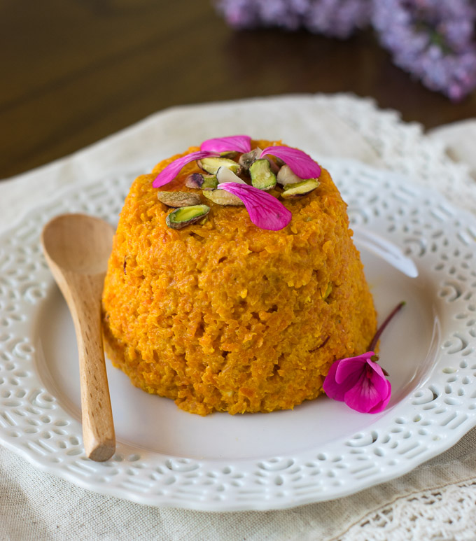 Vegan gajar halwa on a white plate with a spoon.
