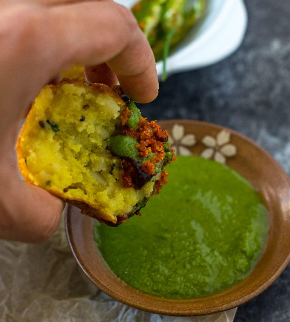 Dipping batata vada in chutney fo eating