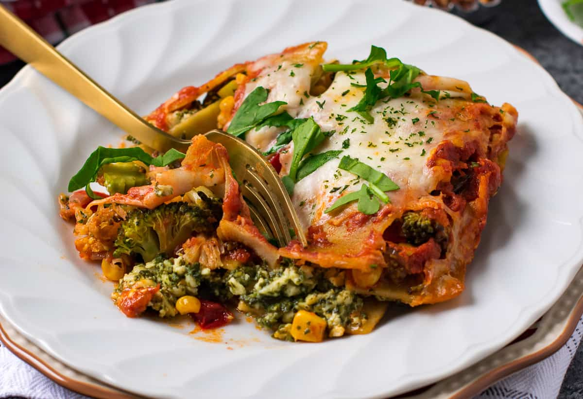 Vegetable lasagna served in a white dish with a fork