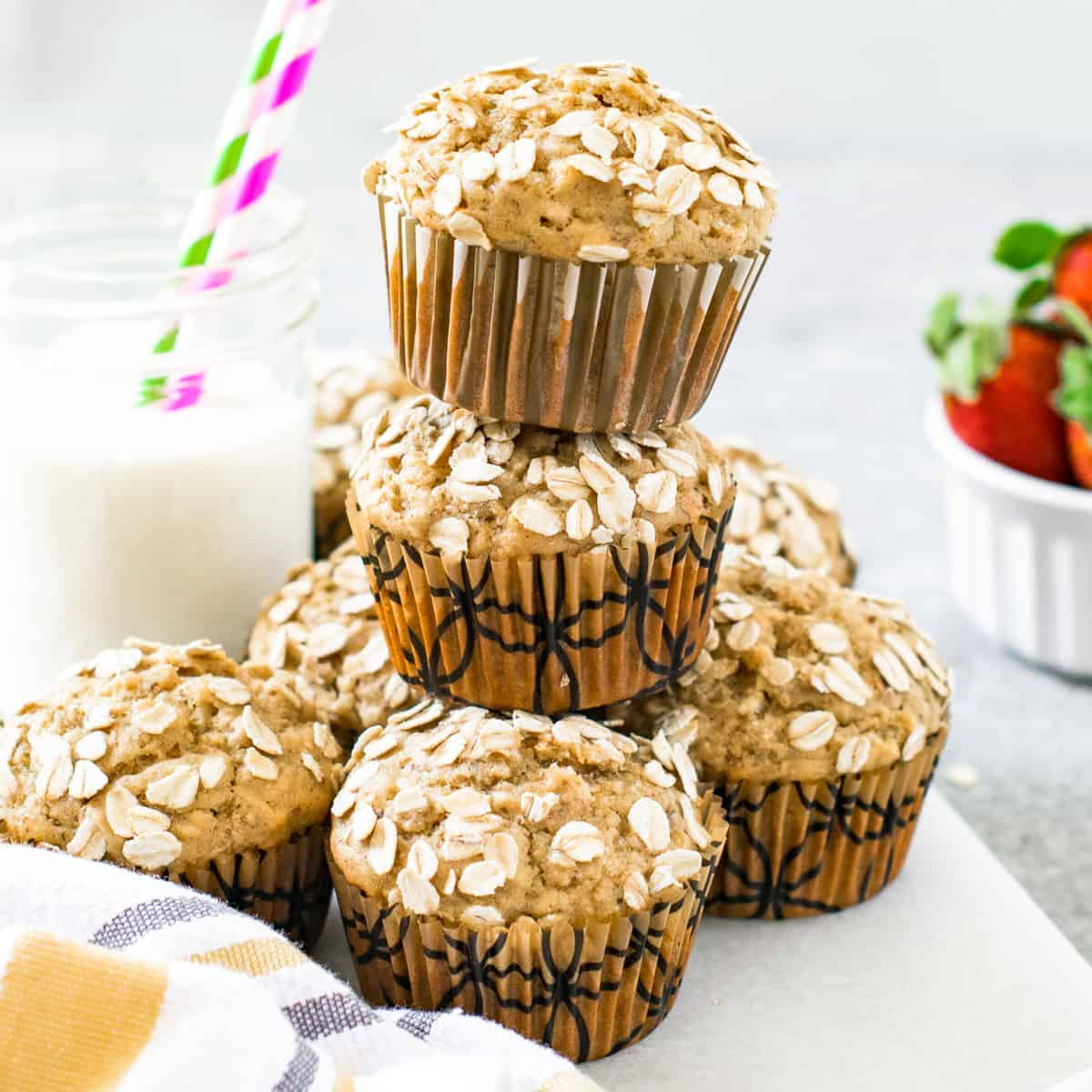 Vegan banana oatmeal muffins stacked together and served besides milk.