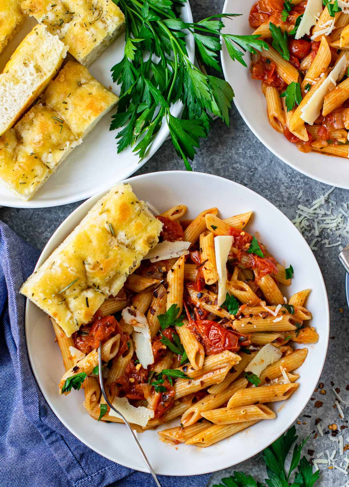 Pasta served on a white plate with some bread on the side