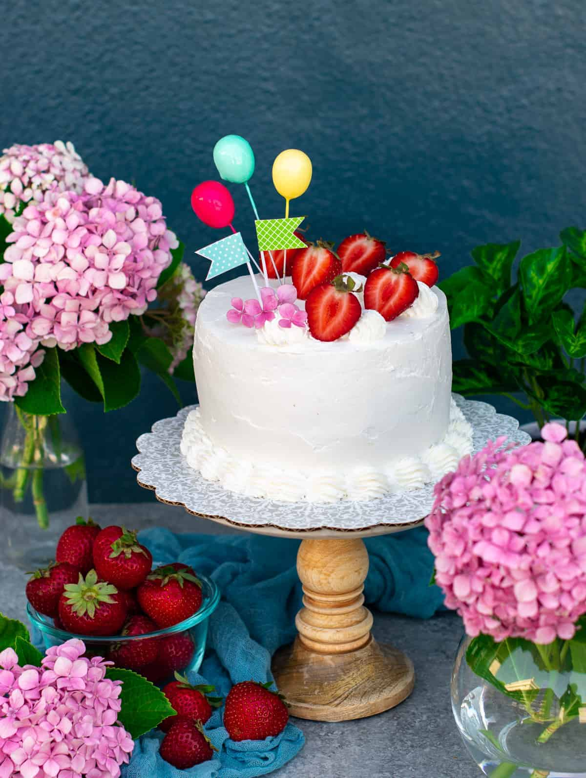 Eggless strawberries and cream cake on a cake stand