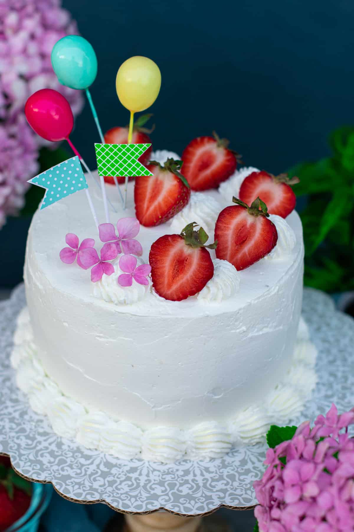 Strawberries and cream cake with pink flowers and balloons as decoration