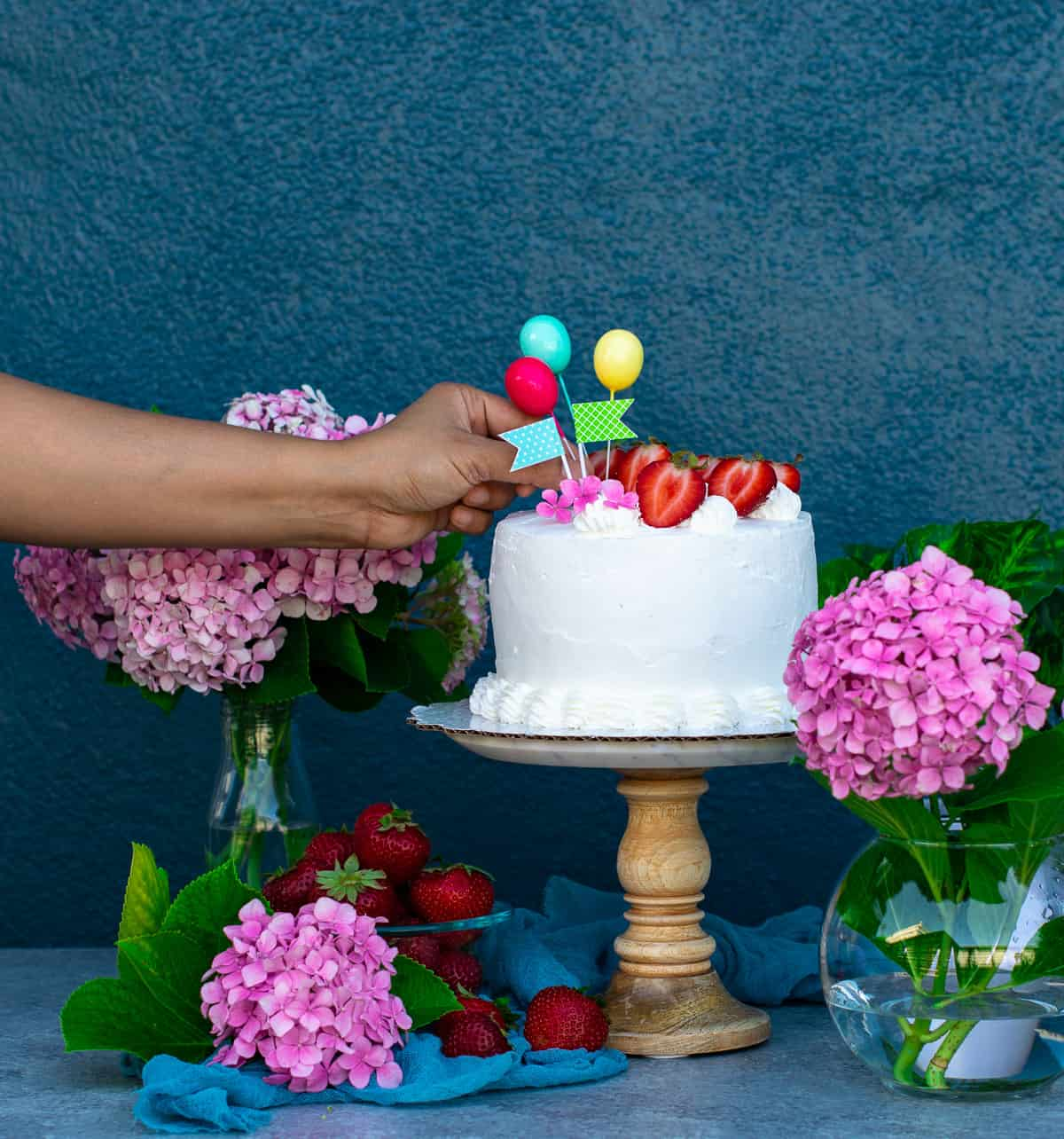Placing balloon toppers on the cake