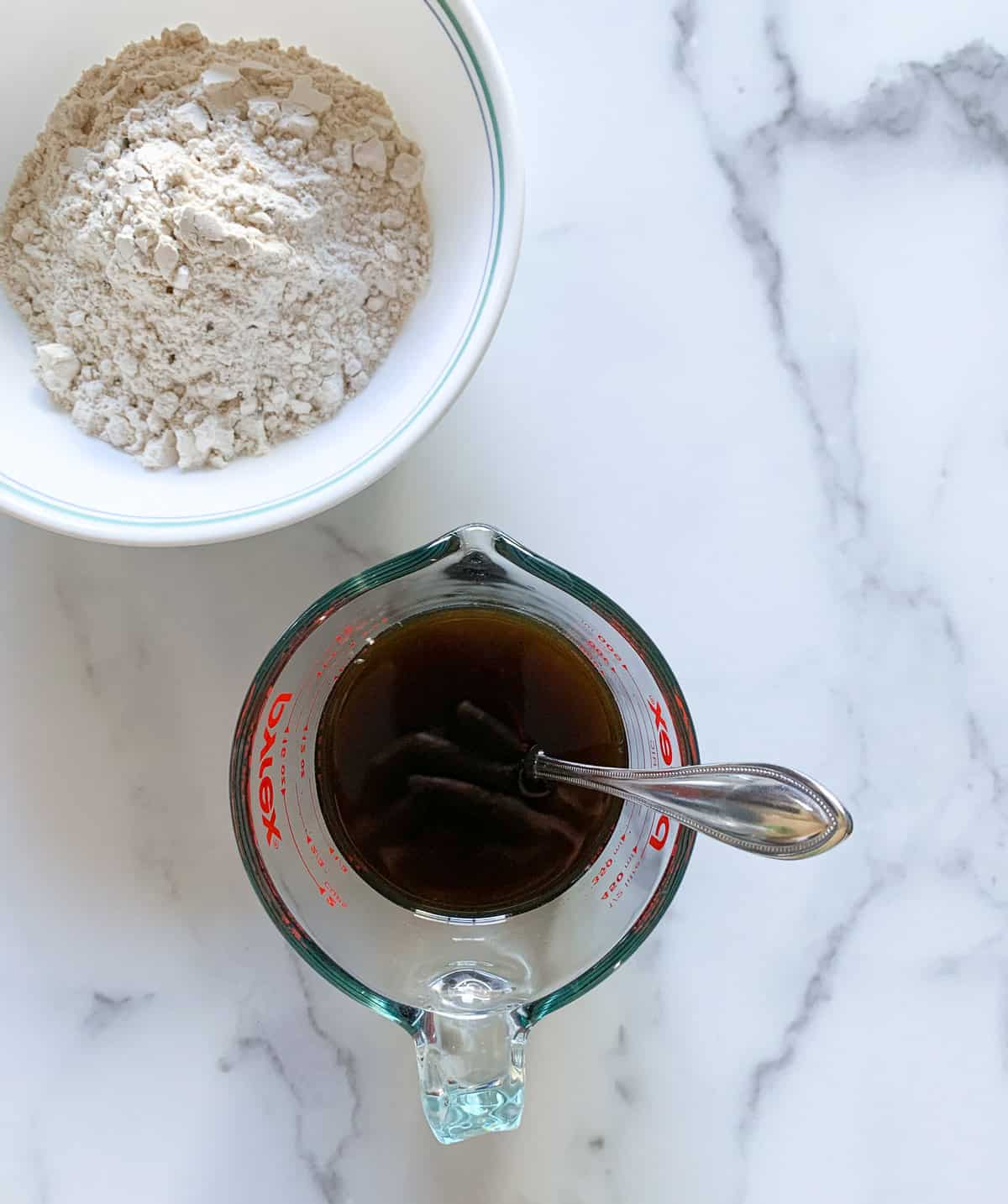 Jaggery melted in a glass measuring cup