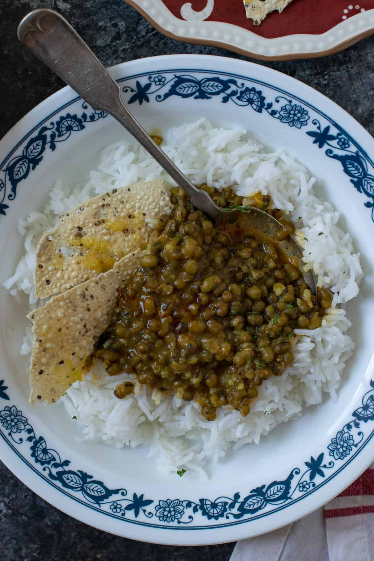 Green mung dal on a white plate over steamed rice