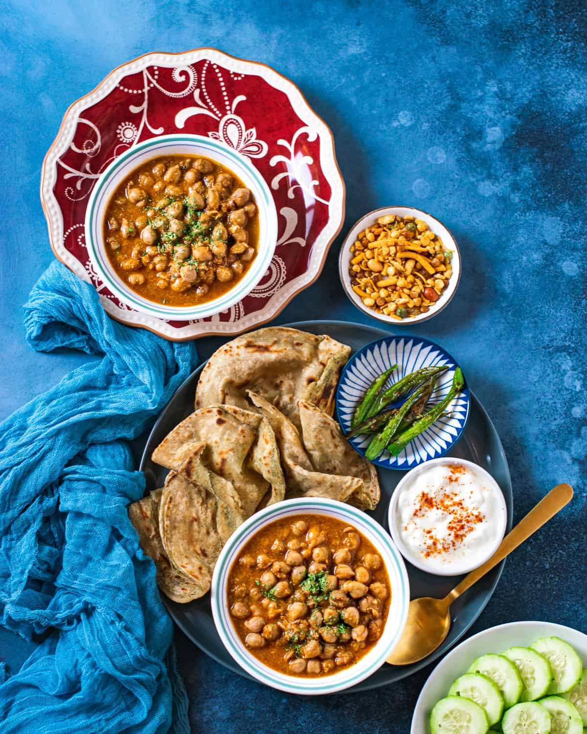 Indian Chickpea Curry served with paratha , fried chilies and yogurt