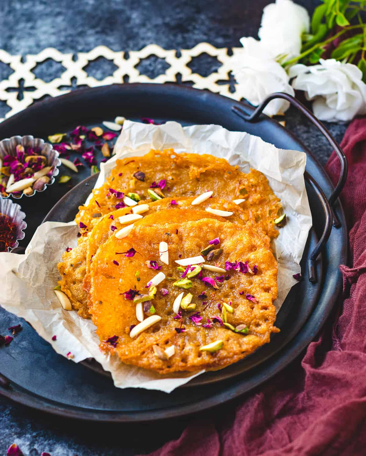 Malpuas on a platter with saffron, rose petals and nuts on the top