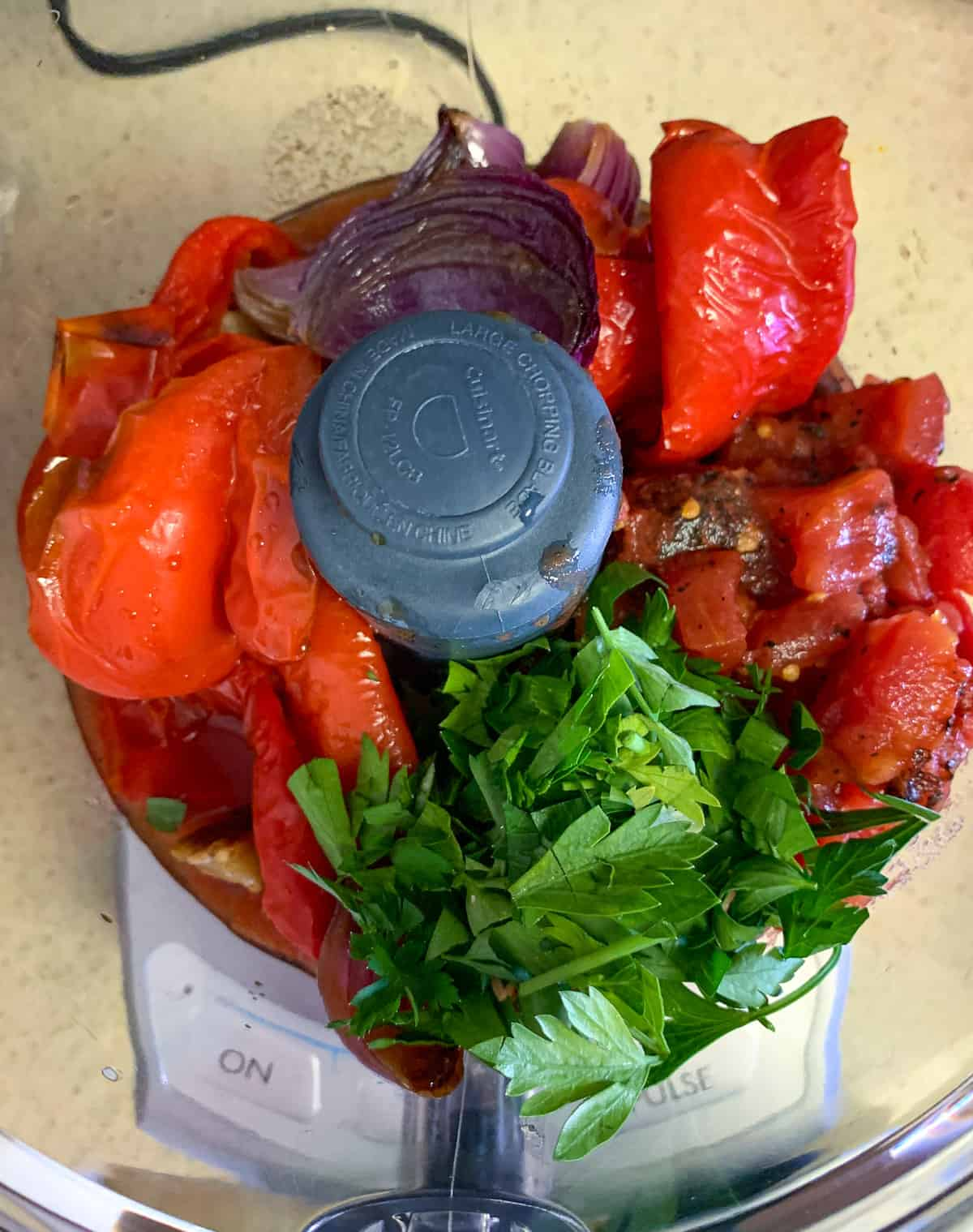 Crushing peppers , tomatoes and other ingredients for the sauce in a food processor
