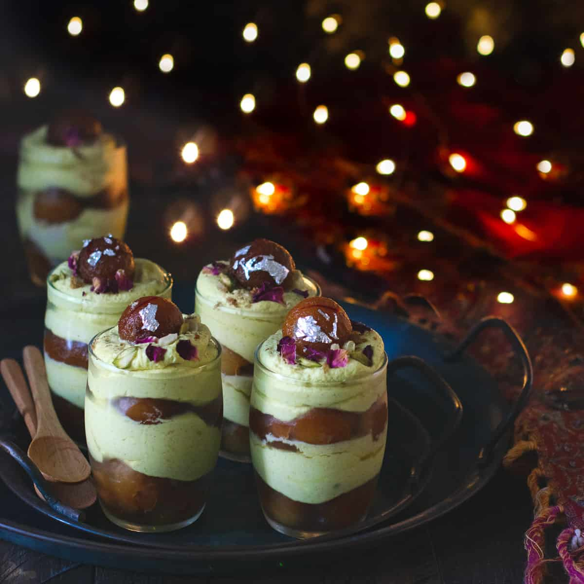 Thandai mousse with gulab jamun with diwali lights as a backdrop