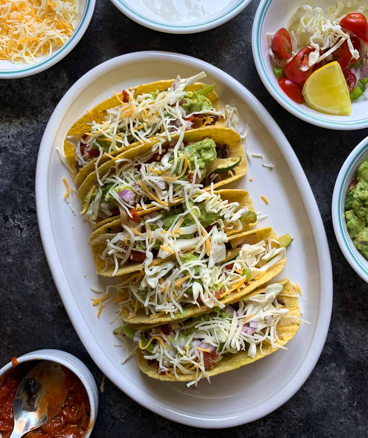 Tacos served on a white platter with other toppings