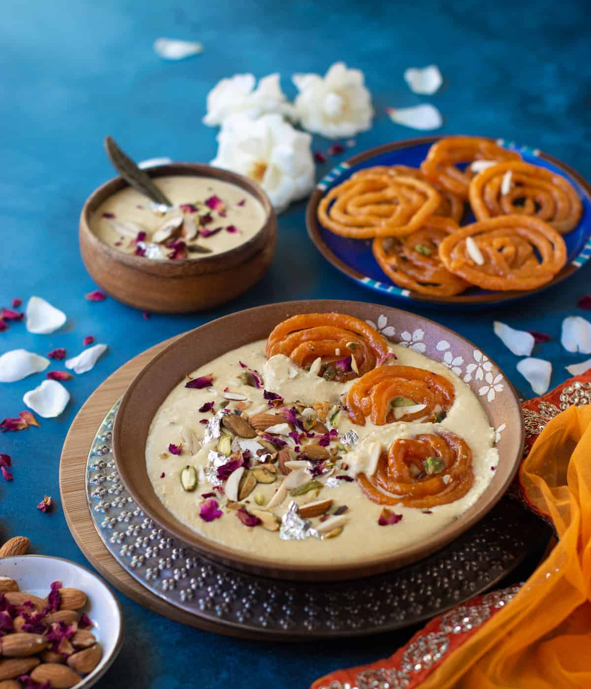 Jalebis and rabdi in a brown dish with more jalebis at the back