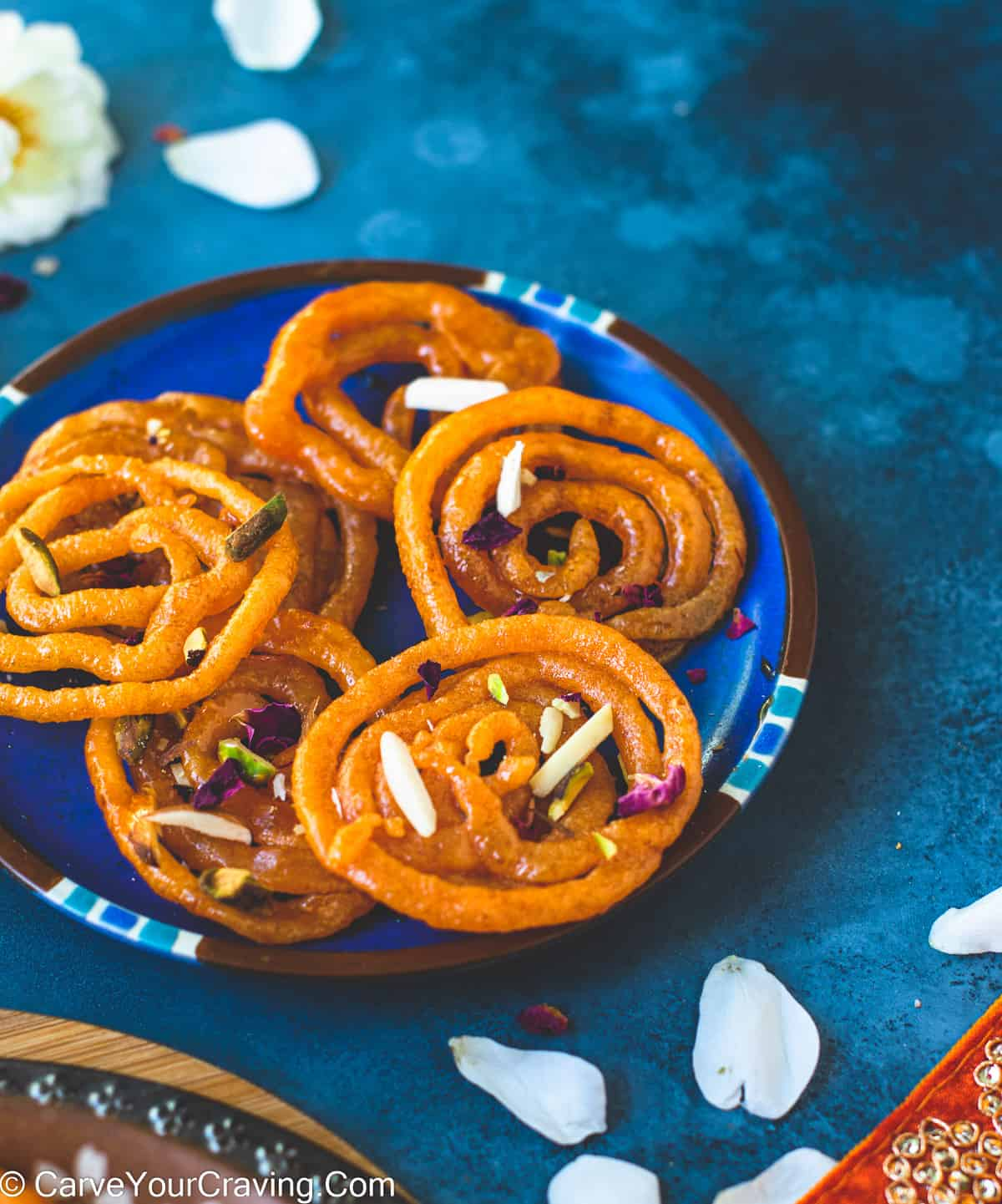 Crispy jalebi on blue plate with nuts on the top