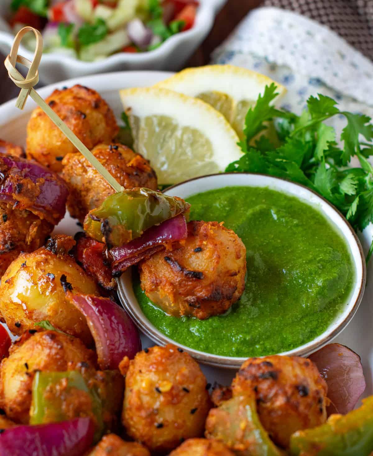 Achari aloo tikka dipped in green cilantro chutney