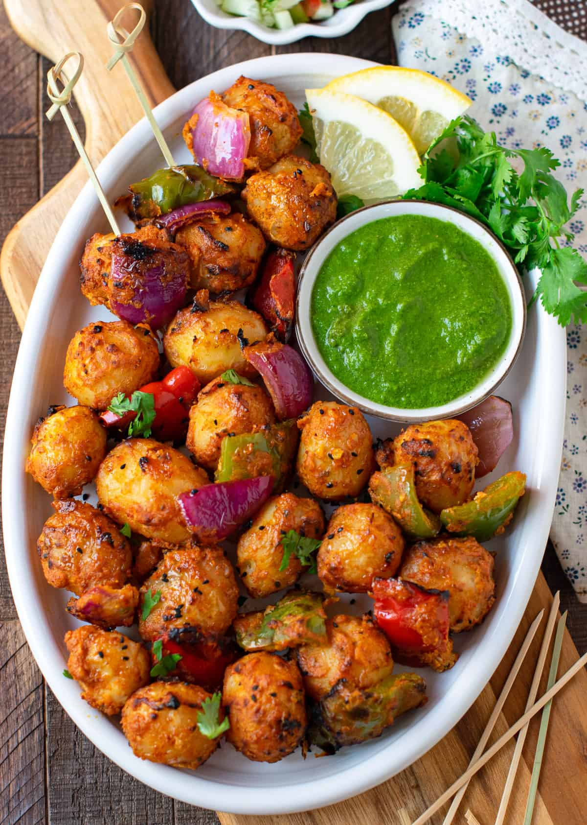 Achari aloo tikka served in a white plate with green chutney