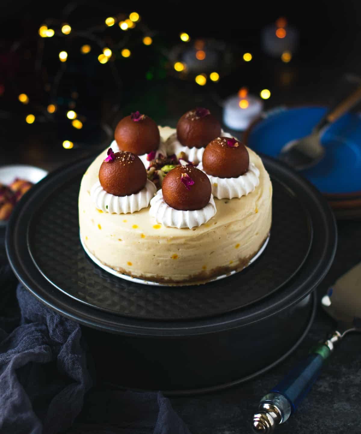 Eggless Gulab Jamun Cheesecake on a black cake stand