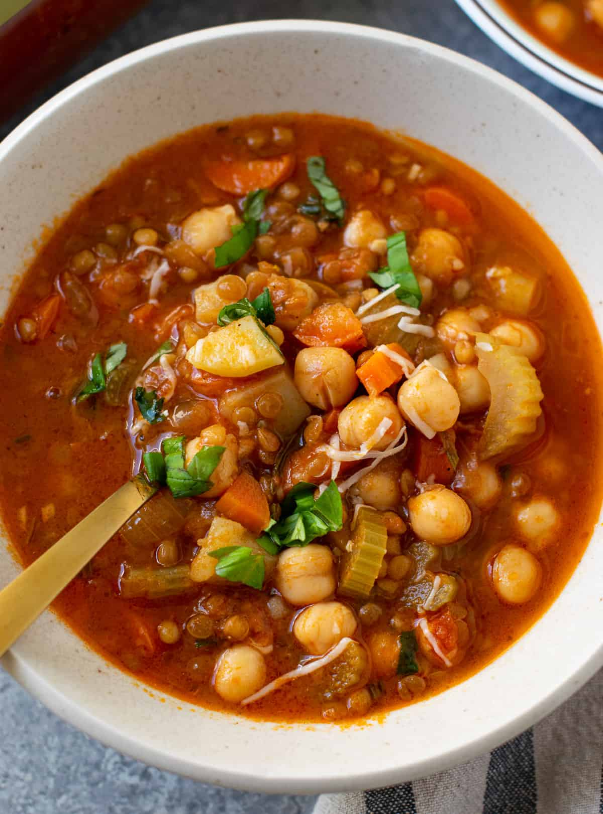 Lentil Soup With Chickpeas Rosemary & Garlic in a bowl with golden spoon