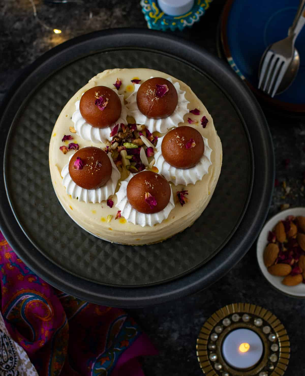 Cheesecake topped with gulab jamun with a side of nuts