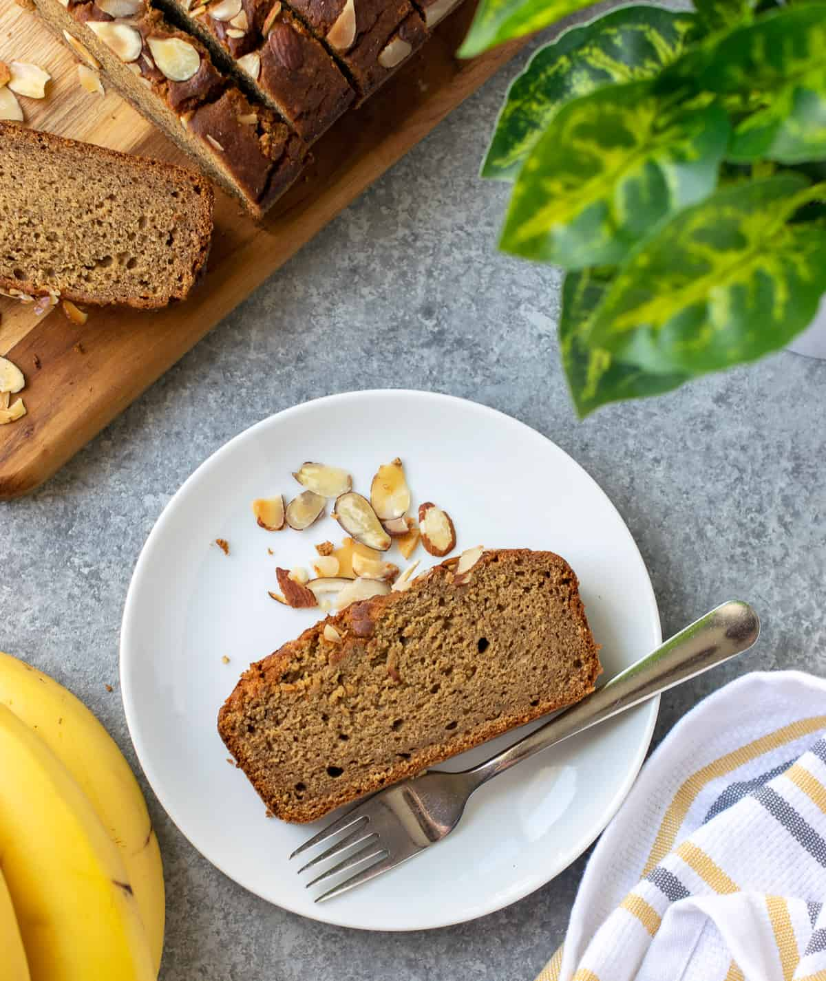 A slice of healthy vegan banana bread on a white plate