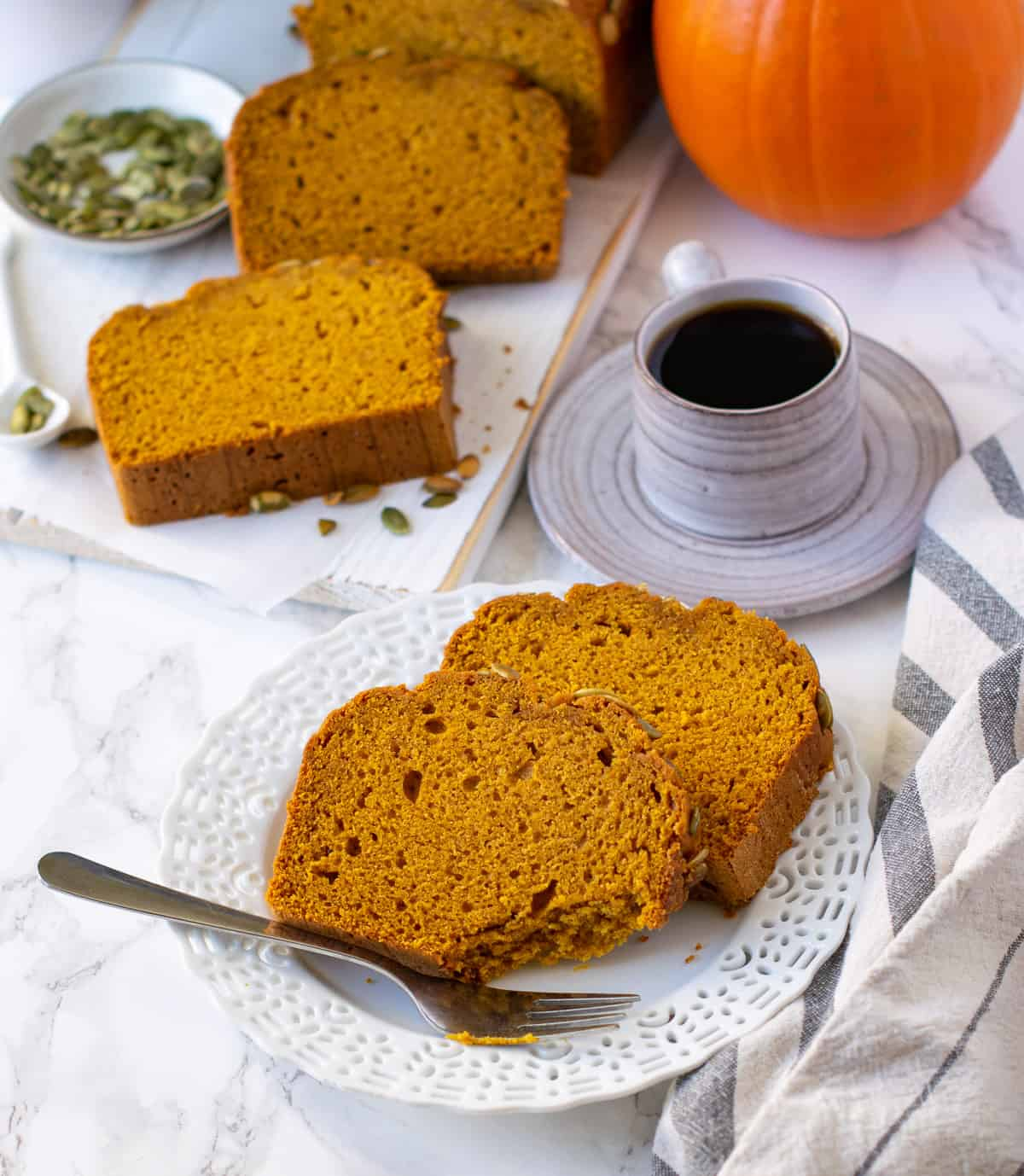 Vegan Pumpkin bread served on a white plate with coffee