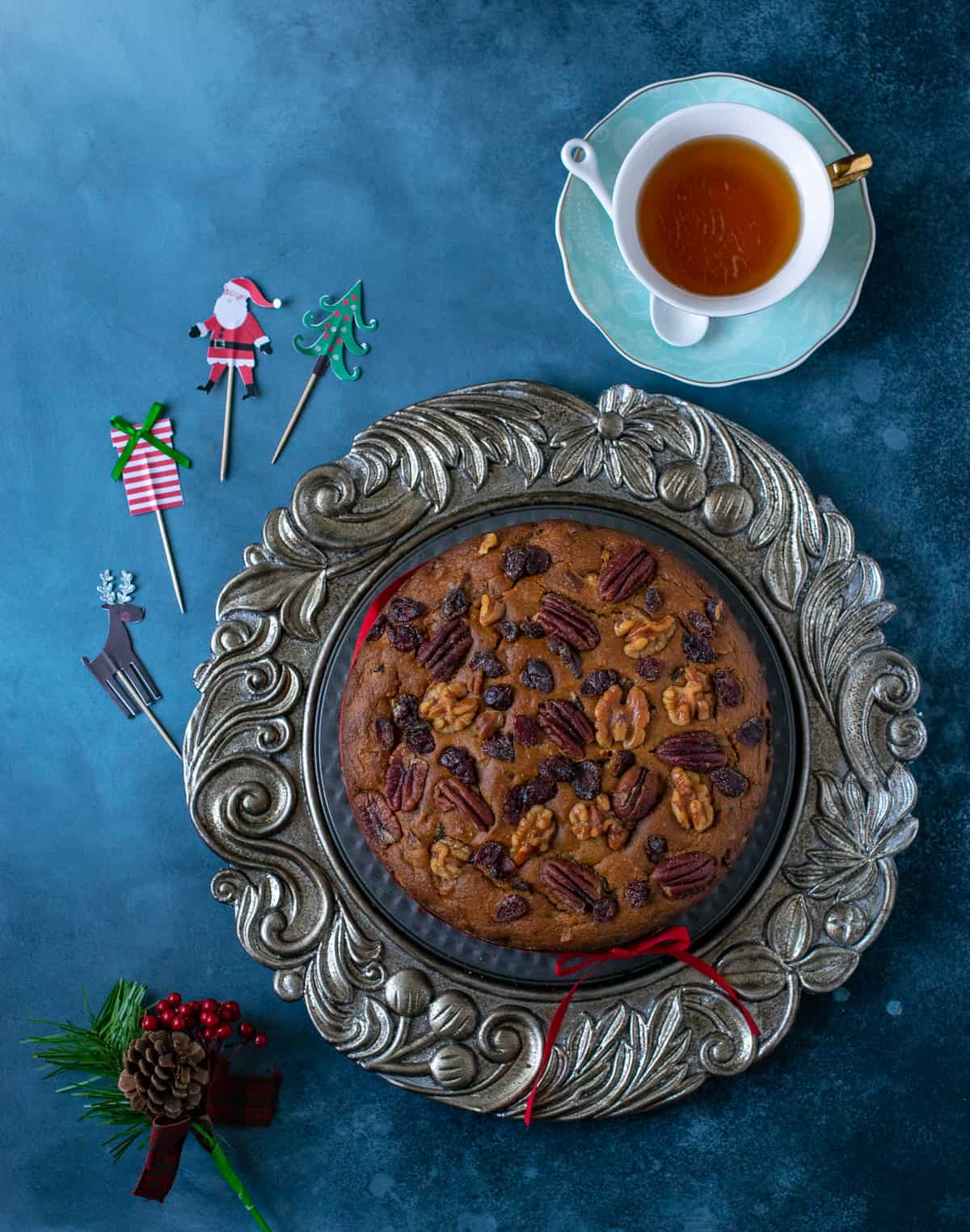 Vegan fruit cake served on a silver platter with tea on the side