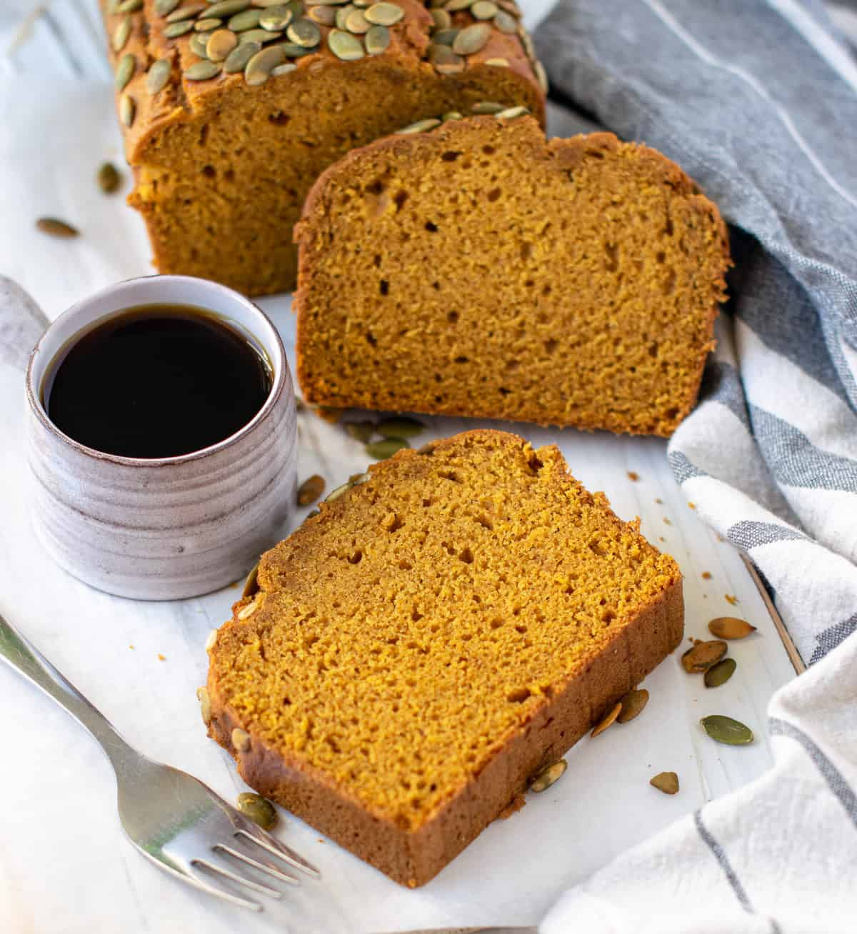 Slices of pumpkin bread served with coffee and a fork