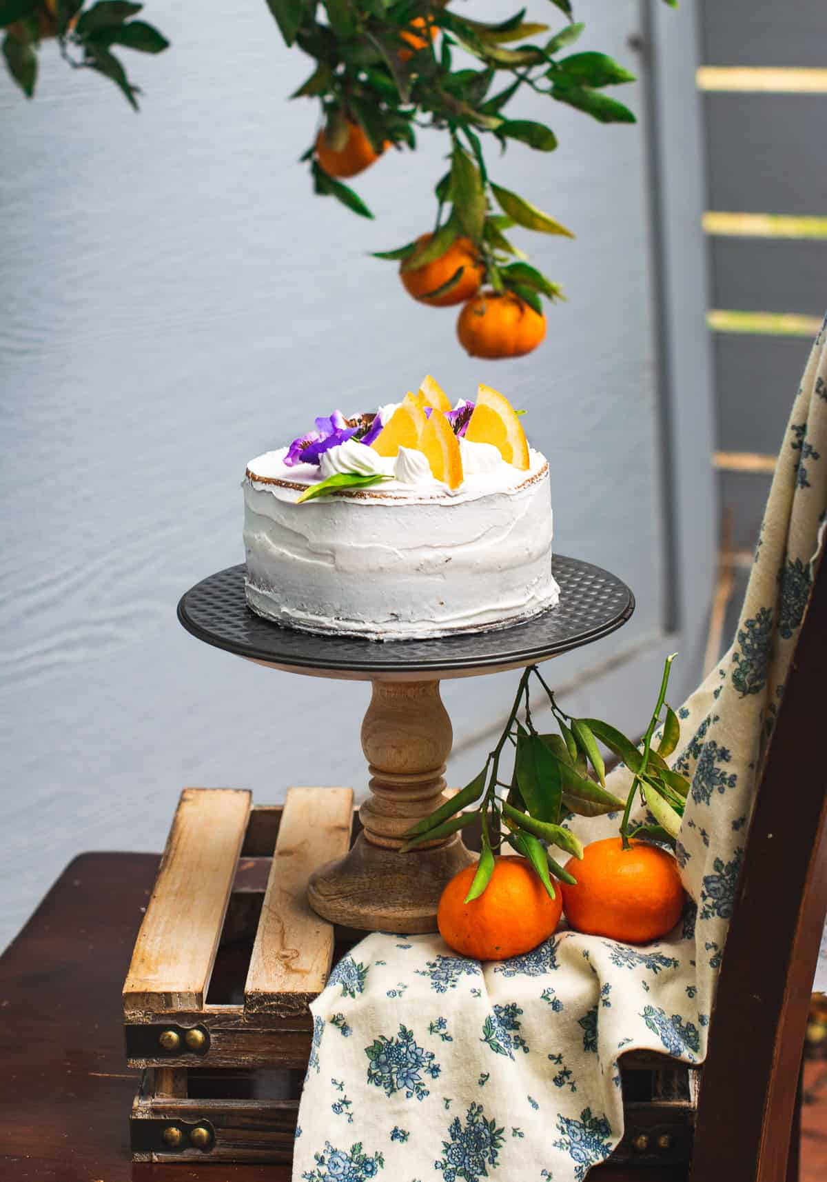 Eggless orange cake frosted and kept on a cake stand