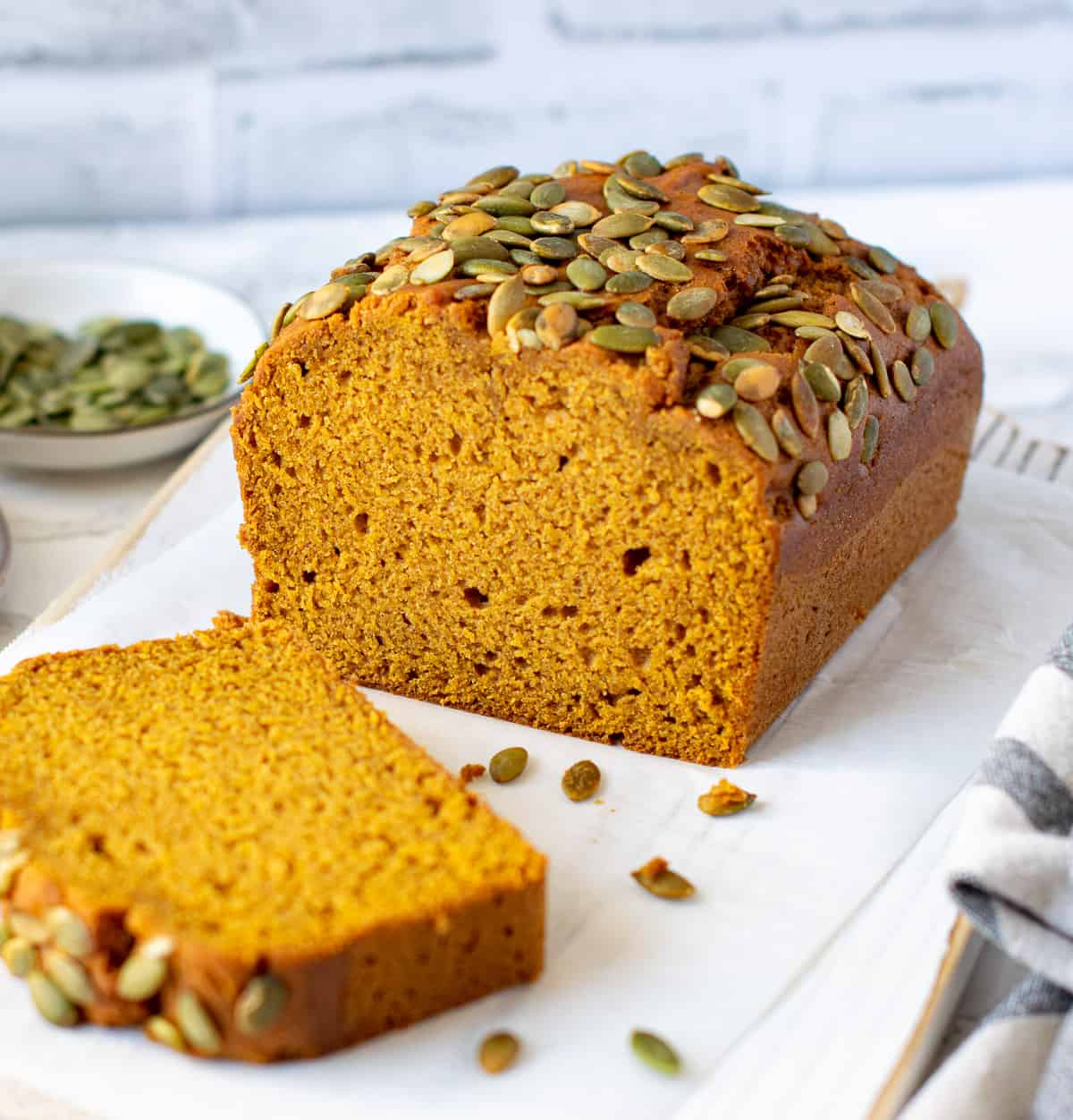 Vegan Pumpkin Bread served on a white board with pumpkin seeds on the side.