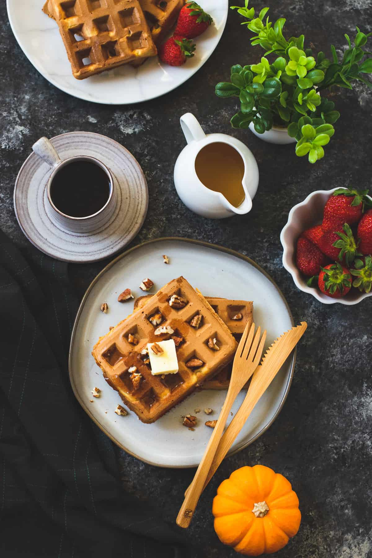 Crispy waffles served with coffee and strawberries on the side
