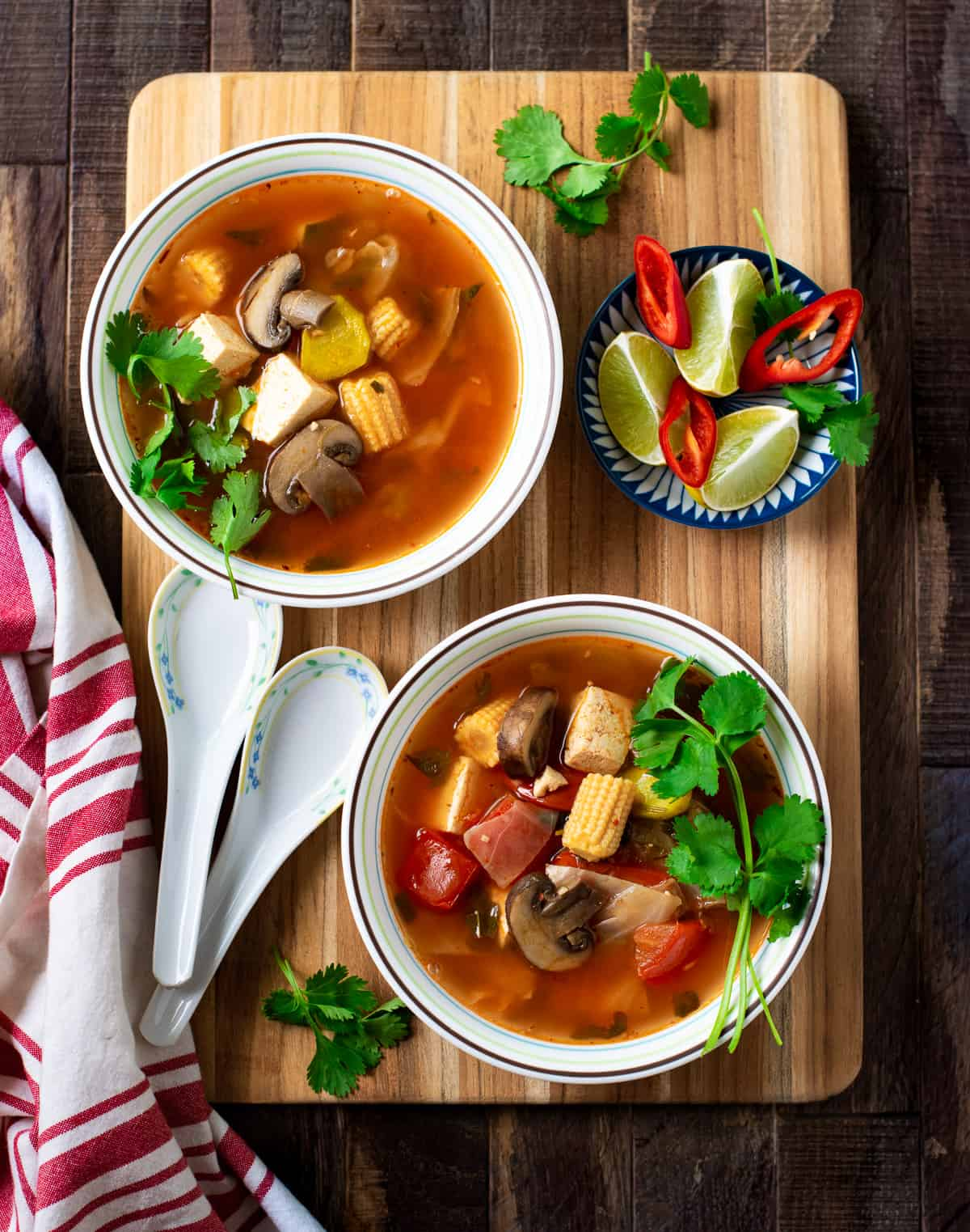 Thai tom yum soup sered in bowls and set on a woodden board