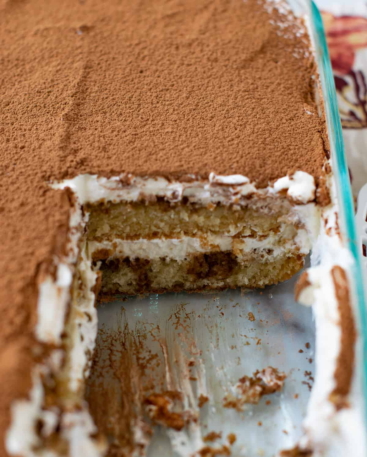 Eggless tiramisu cake sliced and served from a glass pan