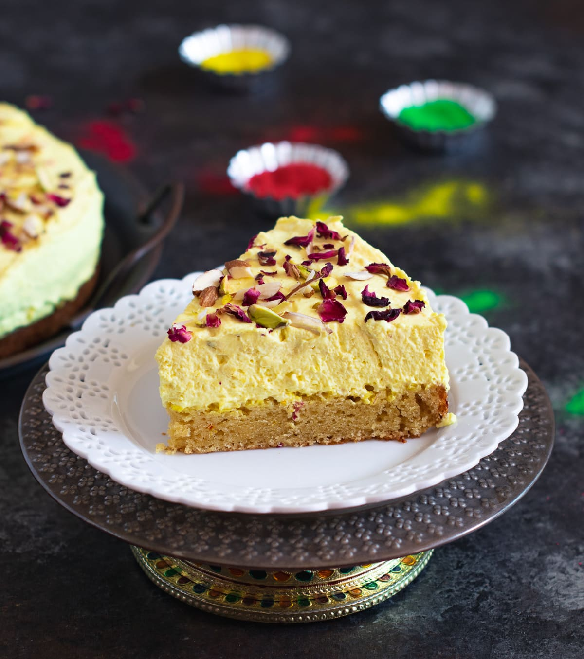 Eggless Thandai Cake set on a white plate over a cake stand.