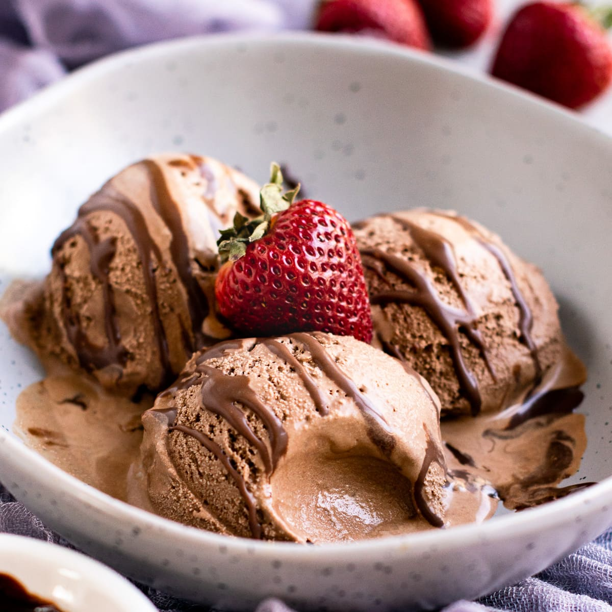 Cuisinart chocolate ice cream in a bowl with strawberry on the top