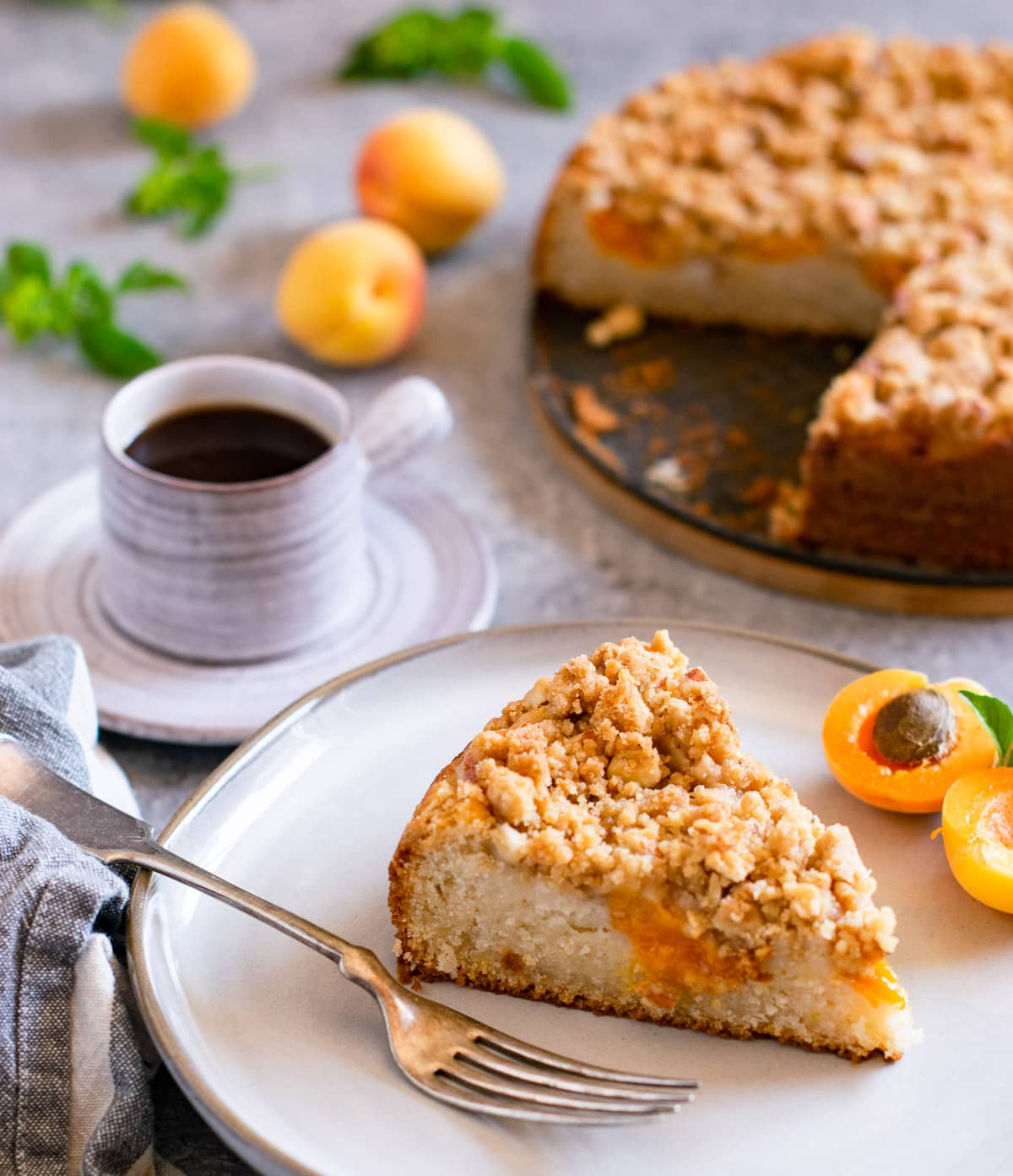 Coffee served with a slice of apricot crumb cake