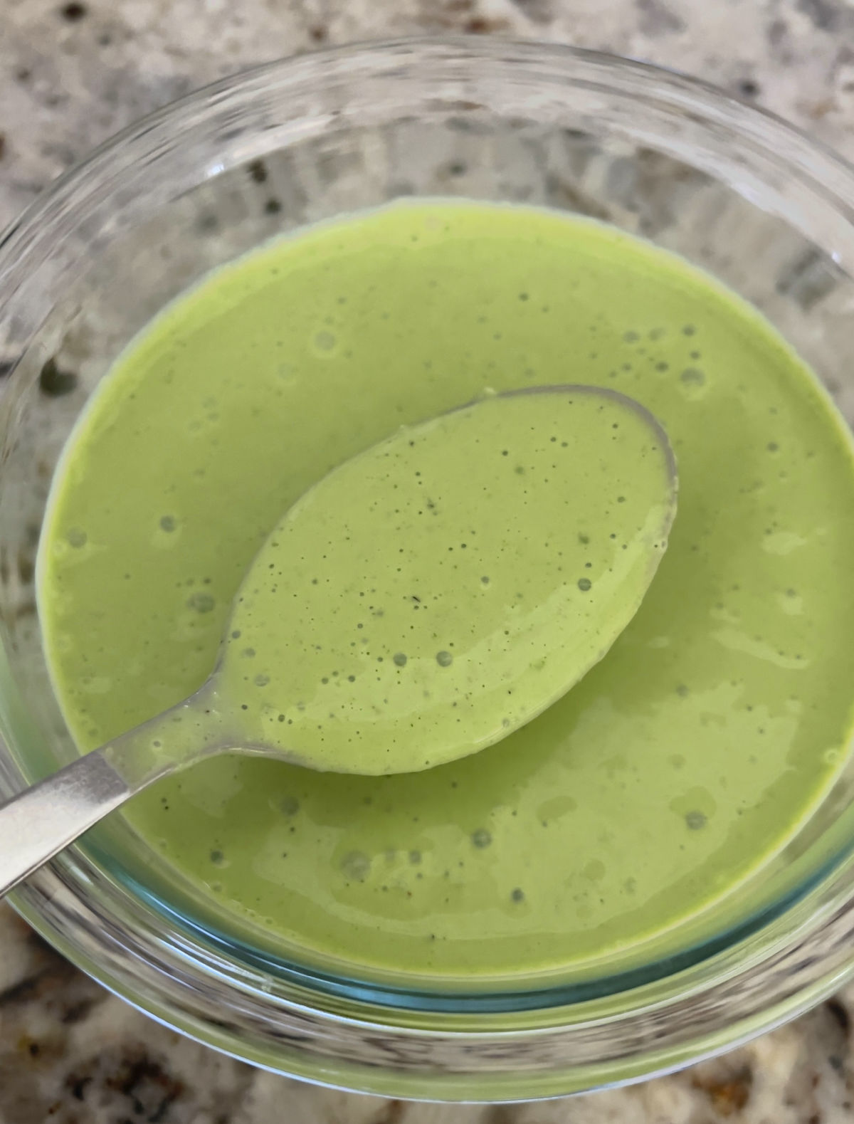 Creamy cilantro mint dressing in a bowl with a spoon