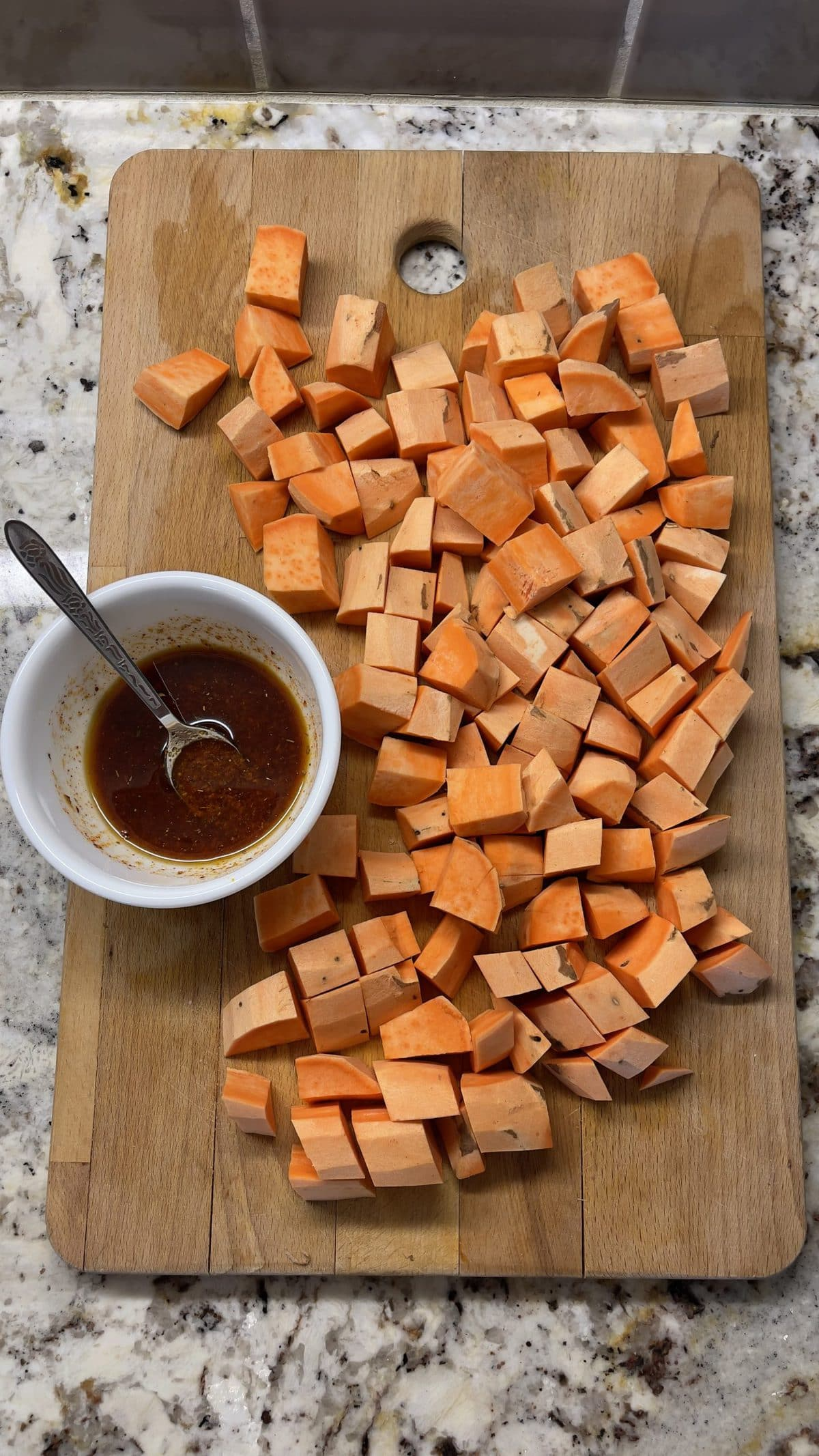 Cubed sweet potato on a cutting board with dressing on the side