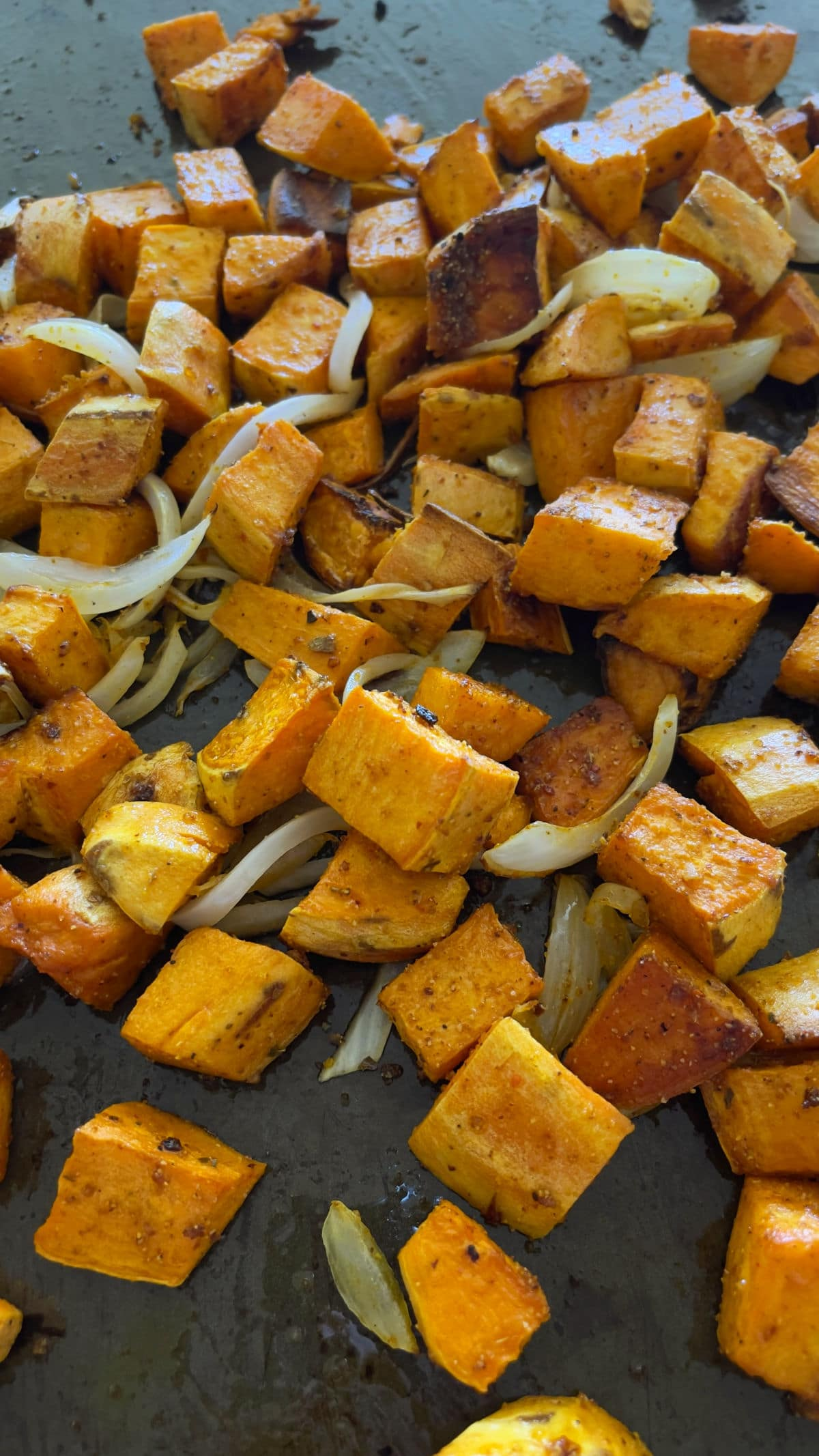 Roasted weet potatoes and onions on a baking tray