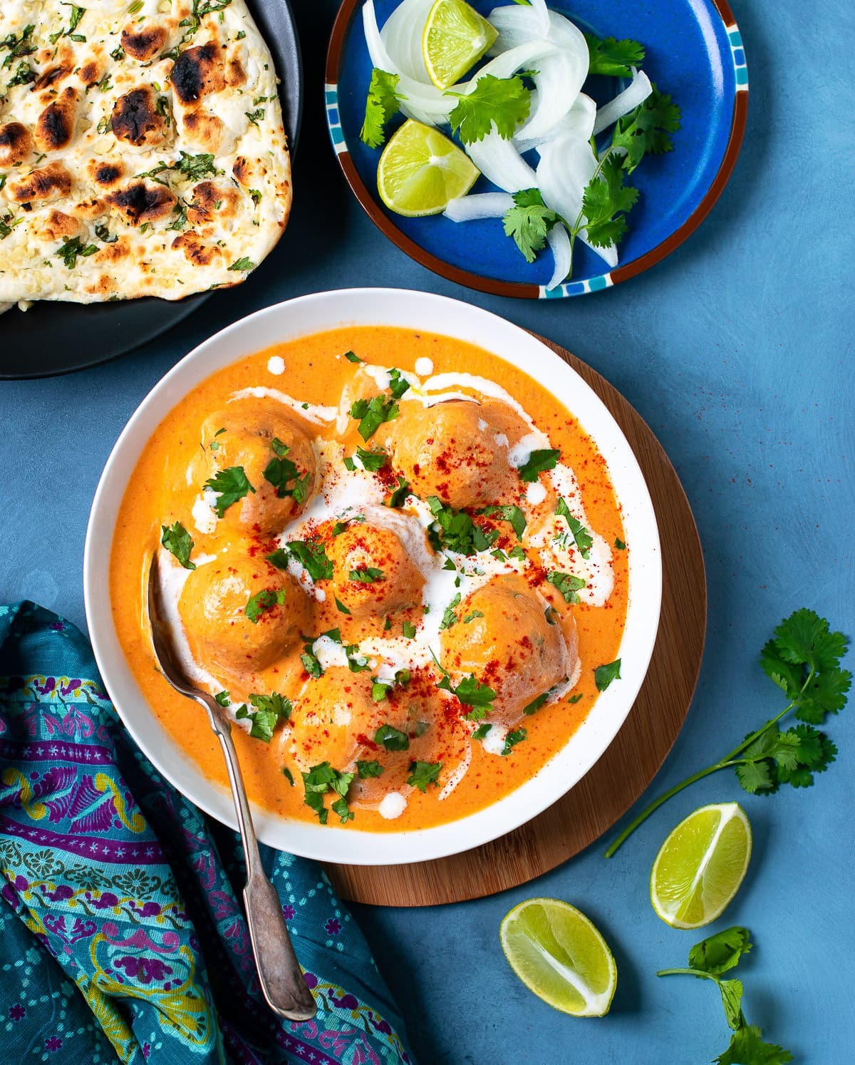 Malai Kofta curry ready to be served with a spoon