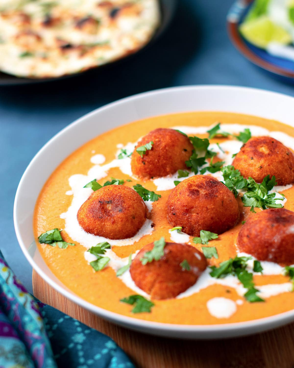 Paneer koftas dunked in Indian gravy and served in a bowl with naan on the side