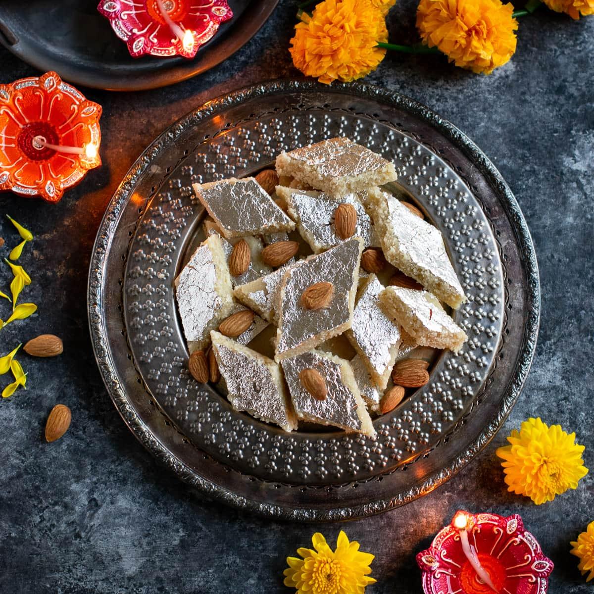 Almond barfi on a dish with marigold and diya on the side