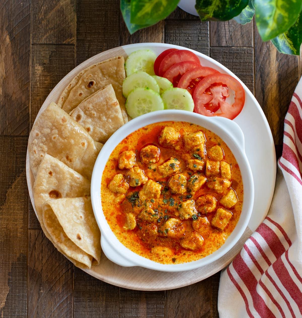 Gatte ki sabji on a white plate with rotis and salad