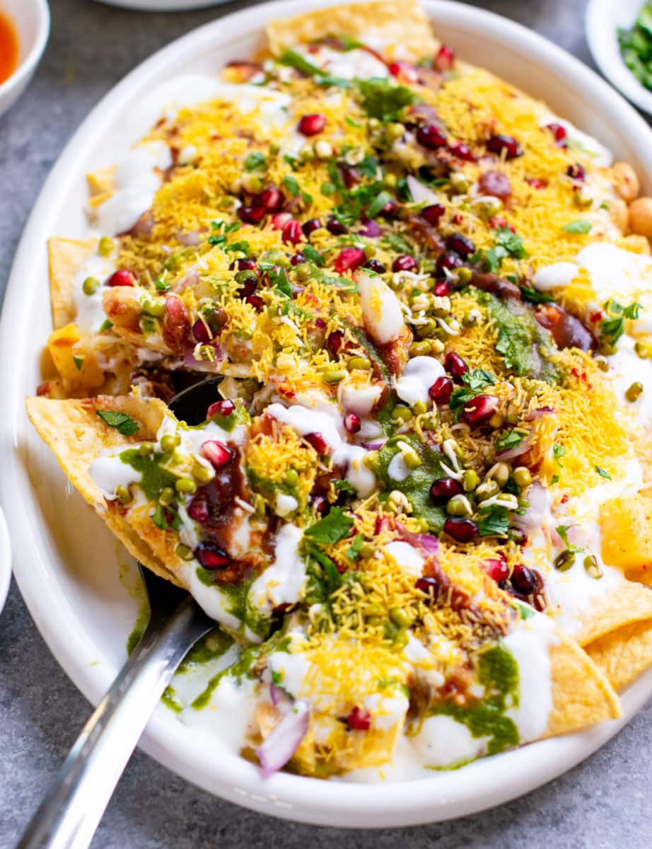 Aloo papdi chaat on a white serving dish with yogurt on the top.